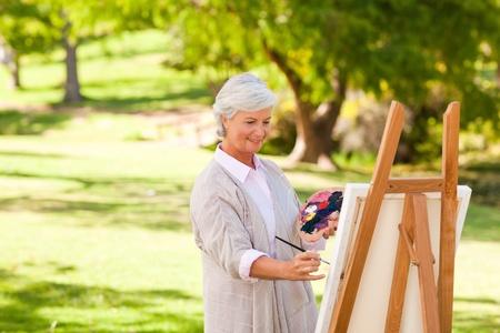 one senior adult woman: Mujer Senior pintura en el Parque Foto de archivo