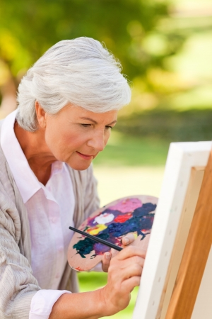 Mature woman painting in the park photo
