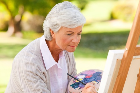 only adult: Mature woman painting in the park