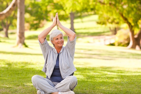Mature woman practicing yoga in the park photo