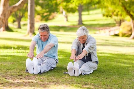 pareja saludable: Pareja de ancianos haciendo sus tramos en el Parque Foto de archivo