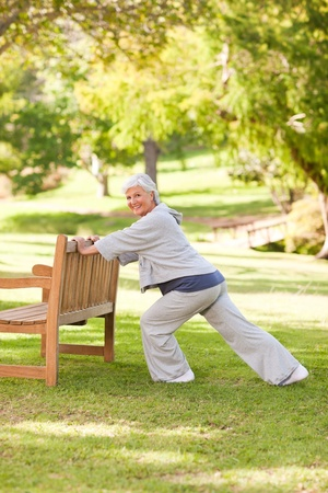 Senior woman doing her stretches in the park photo