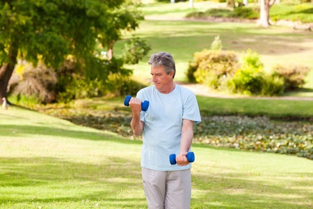 Elderly man doing his exercises in the park Stock Photo - 10218346