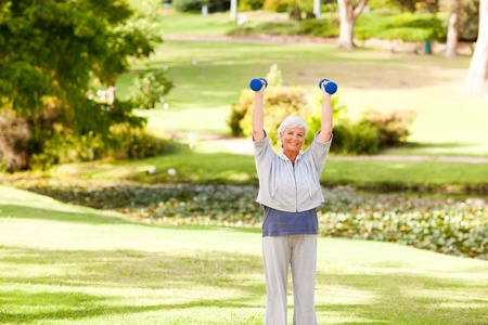 Mature woman doing her exercises in the park photo