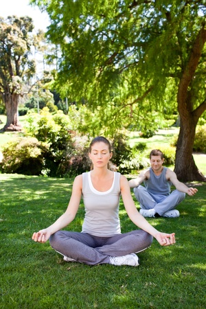 Couple practicing yoga in the park Stock Photo - 10220525