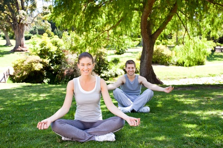 Couple practicing yoga in the park Stock Photo - 10220623