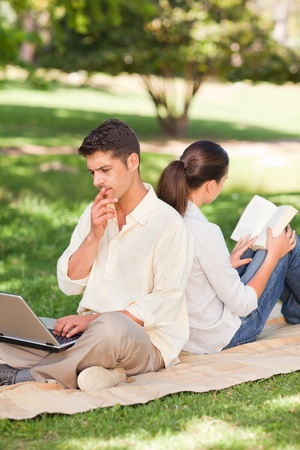 wifi: Man working on his laptop while his wife is reading Stock Photo