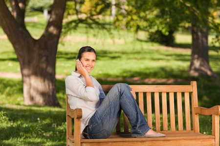 Young beautiful woman phoning on the bench photo