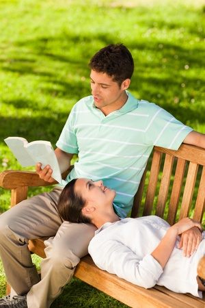 Man reading a book with his girlfriend photo