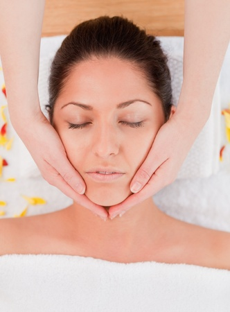 dark-haired woman having a facial massage eyes closed photo
