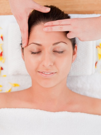 brunette having a forehead massage closing her eyes photo