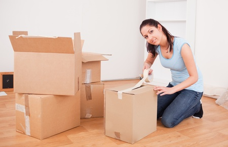 dark-haired woman taping boxes seating on her knees looking athe camera Stock Photo - 10216698