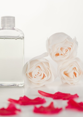 Pink petals with a glass flask and roses photo
