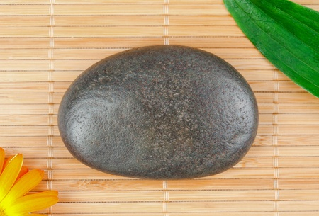 A round smouth pebble surrounded by a leaf and a sunflover photo