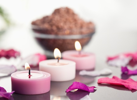 Close up of lighted candles with a brown gravel bowl and petals focus on the candles photo