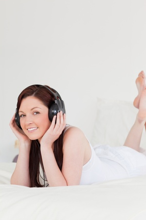 Beautiful red-haired female relaxing with her headphones while lying on her bed photo