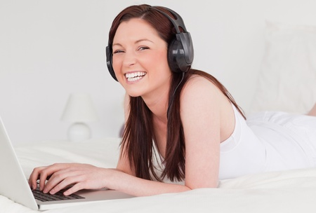 Attractive red-haired female relaxing with her laptop and her headphones while lying on her bed photo