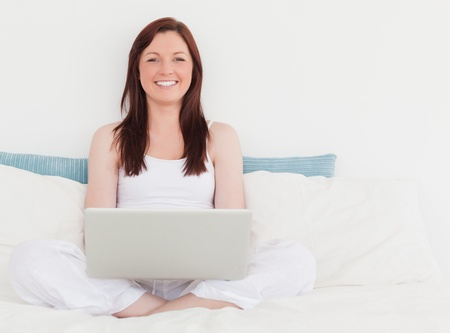 Pretty red-haired female relaxing with her laptop while sitting on her bed photo