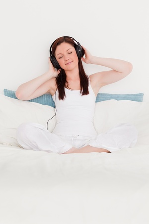 Gorgeous red-haired woman listening to music with her headphones while sitting on her bed photo