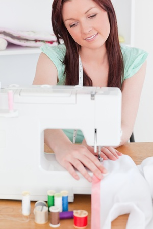 Beautiful red-haired woman using a sewing machine in her living room photo