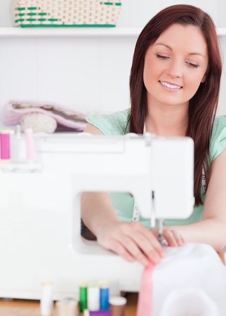 Good looking red-haired woman using a sewing machine in her living room photo