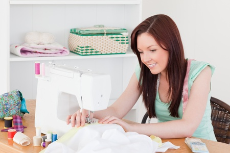 Pretty red-haired female using a sewing machine in her living room photo
