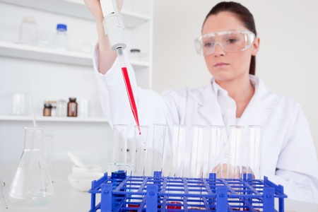 haematologists: Pretty female biologist holding a manual pipette with sample from test tubes in a lab