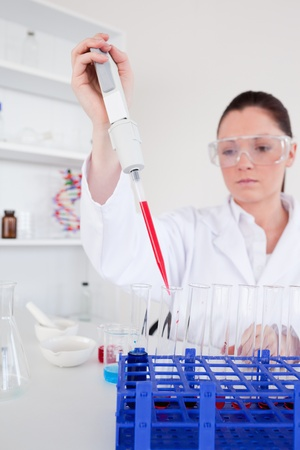 Good looking female biologist holding a manual pipette with sample from test tubes in a lab photo