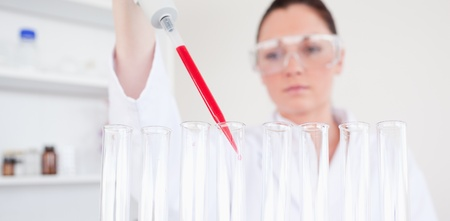 haematologists: Beautiful red-haired scientist filling up a test tube in a lab Stock Photo