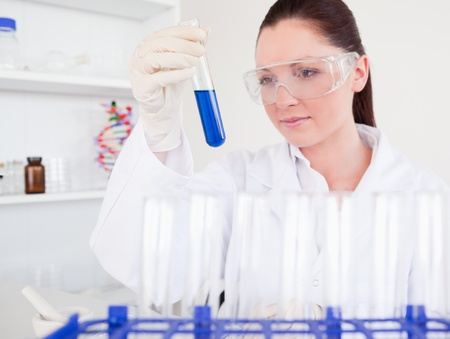 pathology: Beautiful red-haired woman holding a test tube in a lab Stock Photo