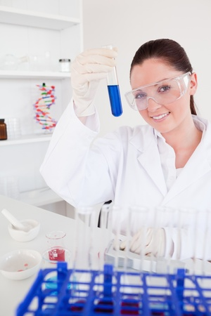 Good looking red-haired woman holding a test tube in a lab photo