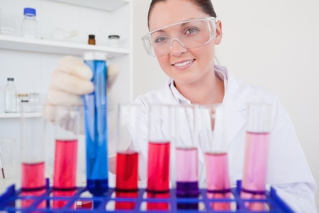 haematologists: Beautiful red-haired female holding a test tube in a lab