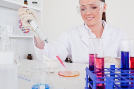 Pretty red-haired scientist using a pipette in a lab photo
