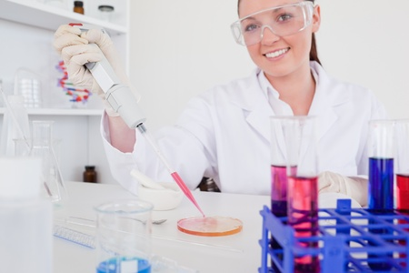 Gorgeous red-haired scientist using a pipette in a lab photo