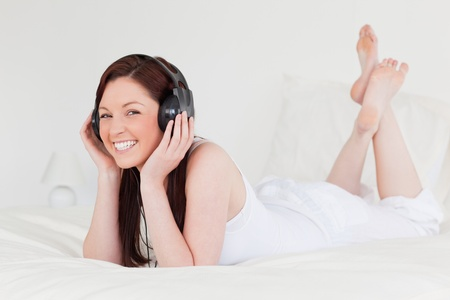 Attractive red-haired female relaxing with her headphones while lying on her bed photo