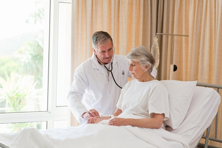 Senior doctor taking the heartbeat of his patient Stock Photo - 10215537