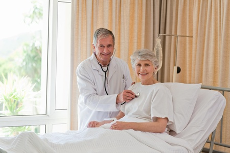 Senior doctor taking the heartbeat of his patient Stock Photo - 10216000