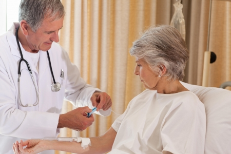 Doctor putting a drip on the arm of his patient Stock Photo - 10217120