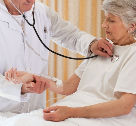 Senior doctor taking the heartbeat of his patient Stock Photo - 10214637