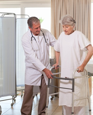 Senior doctor helping his patient to walk photo