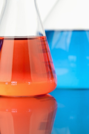 Blue and red beakers against a white background photo