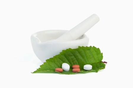Mortar and pestle with pills on a leaf against a white background