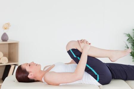 masaje deportivo: Mujer atlética estirando su pierna