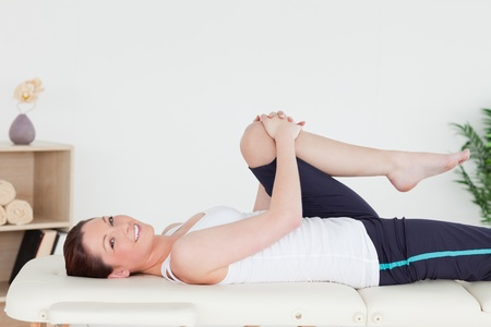 physical pressure: Athletic woman stretching her leg while looking at the camera