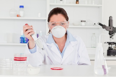 Young scientist preparing a sample wearing a mask photo