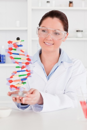 Cute scientist showing the dna double helix model photo