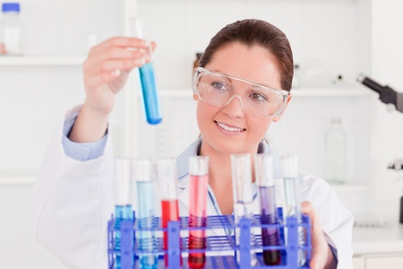 Young scientist looking at test tubes photo
