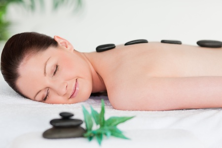 tranquil: Young woman with massage stones on her back eyes closed