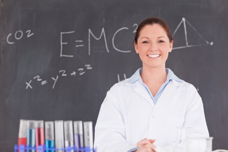 Cute scientist standing in front of a blackboard looking at the camera photo