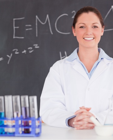 Smilling scientist stanting in front of a blackboard photo